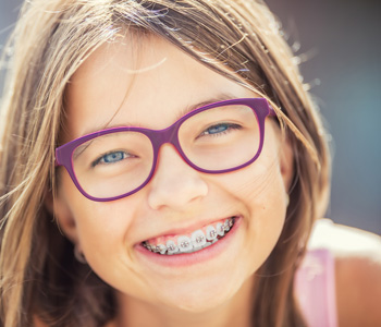 Happy smiling girl with dental braces