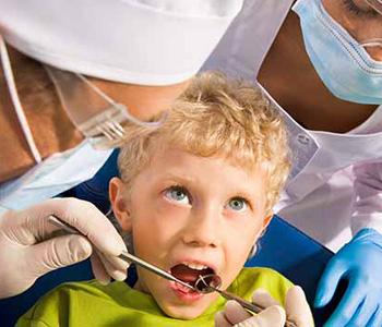 Dentist checking kids' teeth gently