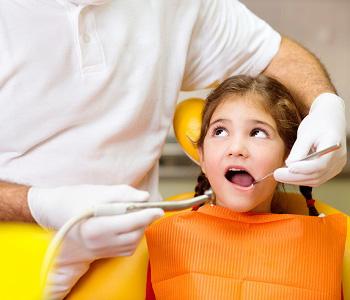 Dentist checking little girl's teeth