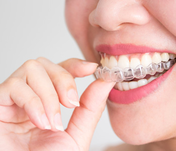A smiling woman holding invisalign