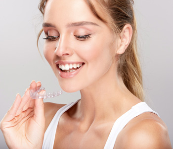 A woman holding Invisalign