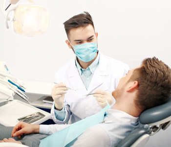 A young male dentist and a patient