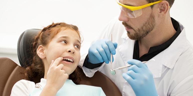 Dentist examining a girl's teeth